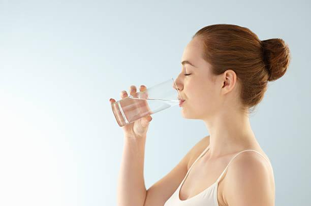 Jeune femme qui boit un verre d'eau filtrée