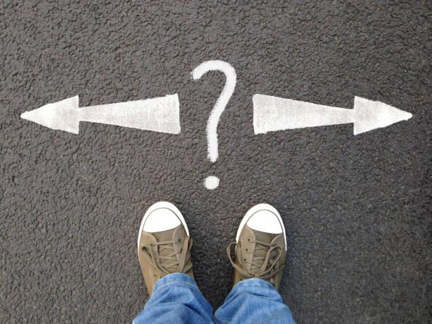 Personne en baskets face à des flèches blanches tracées au sol pointant à droite et à gauche avec un point d'interrogation