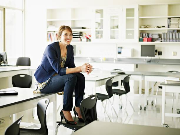 Femme habillée en business woman assise sur un bureau