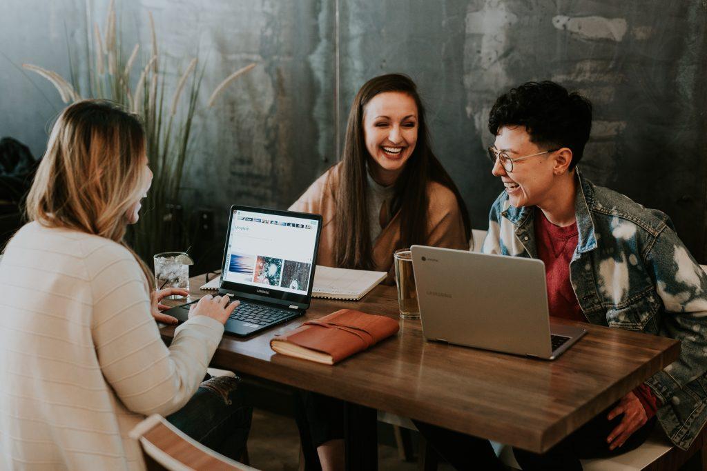 personnes travaillant sur ordinateur et riant ensemble