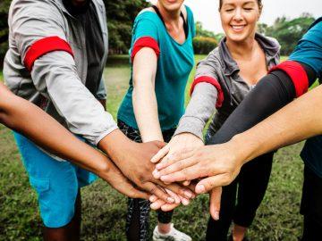 personnes portant un brassard rouge formant une équipe joignant les mains au centre