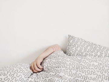 Une personne qui est couchée et qui a son bras sorti sur la couette