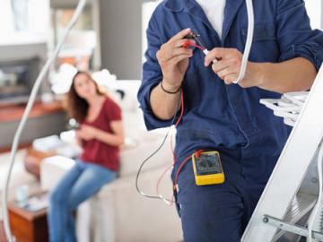 homme en combinaison de travail avec outil d'électricité et femme assise en arrière plan