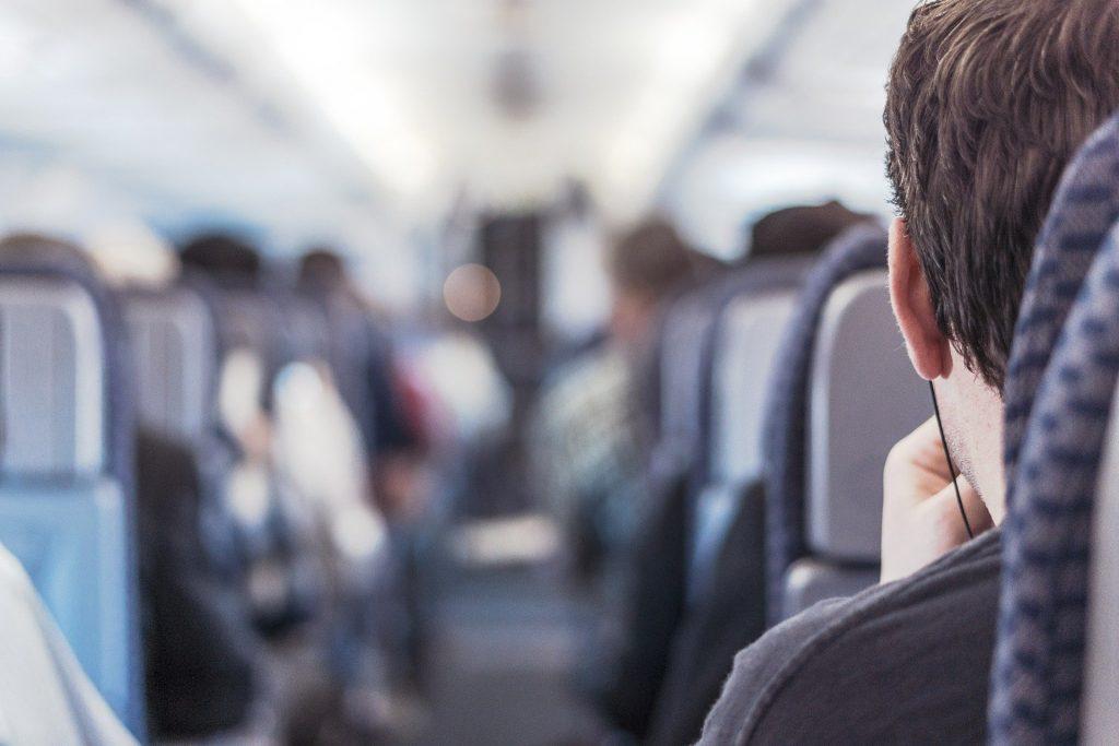 Passager d'un train de dos qui porte des écouteurs