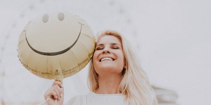 Jeune femme avec une bonne santé bucco-dentaire qui sourit à pleines dents