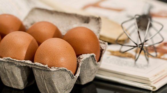 oeufs, fouet et livre de recettes posés sur une table